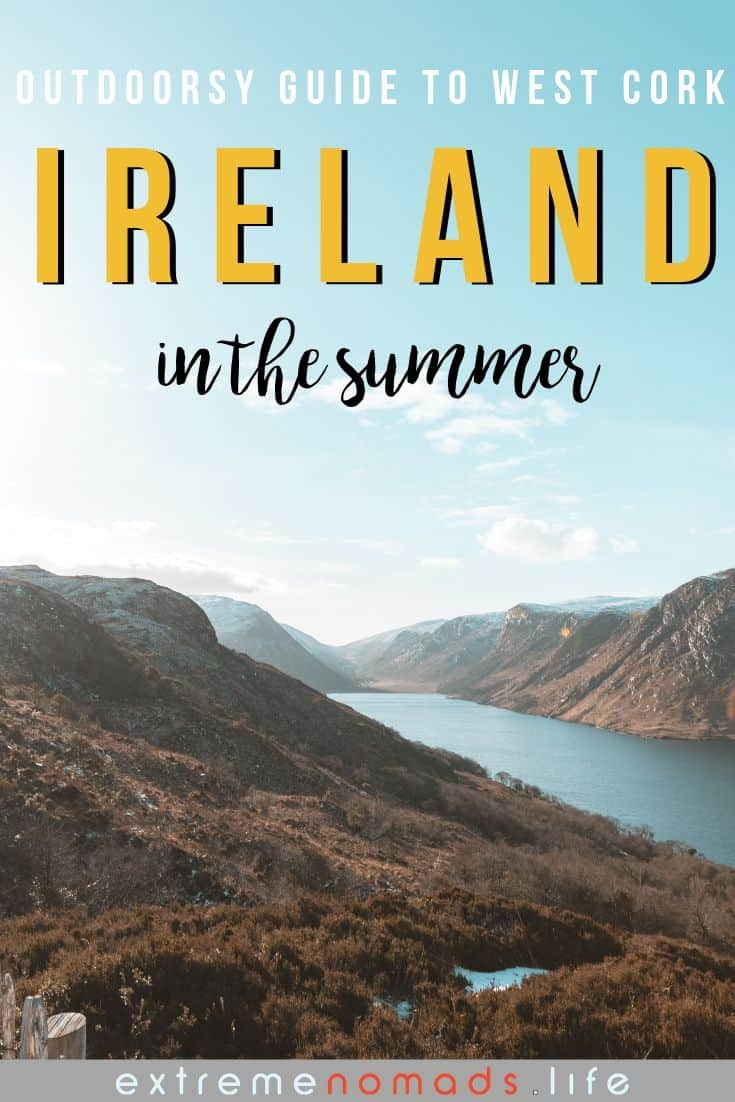pinterest image with a beautiful view of heather covered mountains and a glassy blue lake, with a hazy pale blue sky above. the caption reads: outdoorsy guide to west cork, ireland, in the summer'