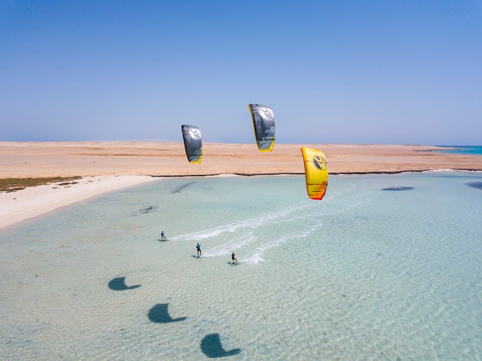 three kitesurfers ride in unison on the azure waters of el gouna, egypt, with desert in the background and a clear blue sky above