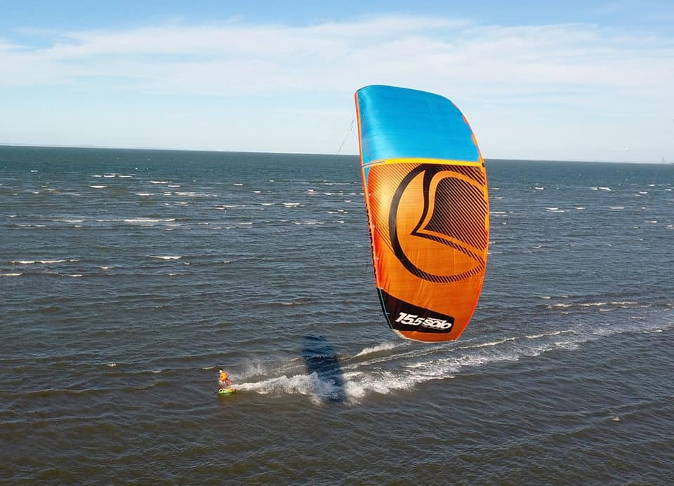 grey choppy waters of queensland, australia, with a kitesurfer riding from right to left, flying a 15m orange and blue cabrinha kite