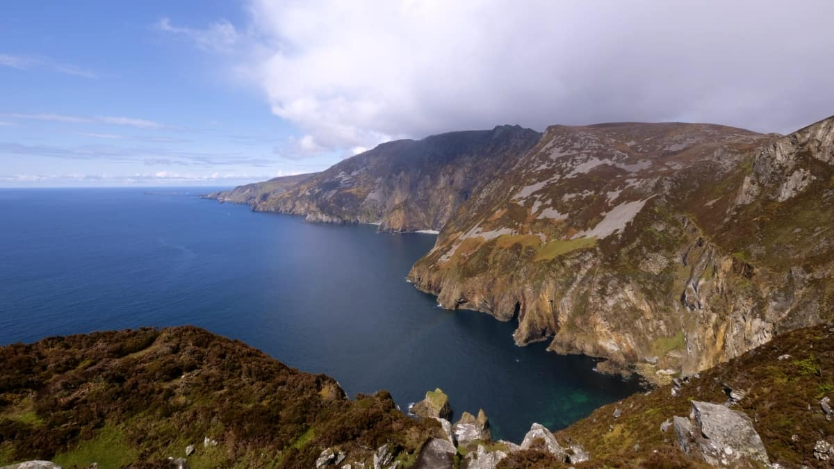 calm blue water on the left meets the rusty and grassy coloured mountains of slieve league. the faint colours of a rainbow appear between the cliffs in the foreground.