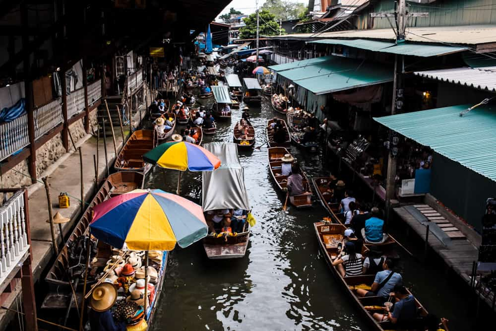 one of bangkok's floating markets viewed from above. the canal is busy with small boats -- some carrying tourists and others holding the vendors and their wares. green roofs cover part of the canal on the right, while rainbow coloured umbrellas shield some boats on the left from the bright sunlight