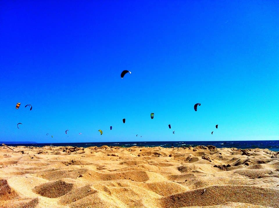 electric blue sky and golden sand of the kitesurfing beach in cascais, portugal. a dozen or so kites fly in the air above the water.