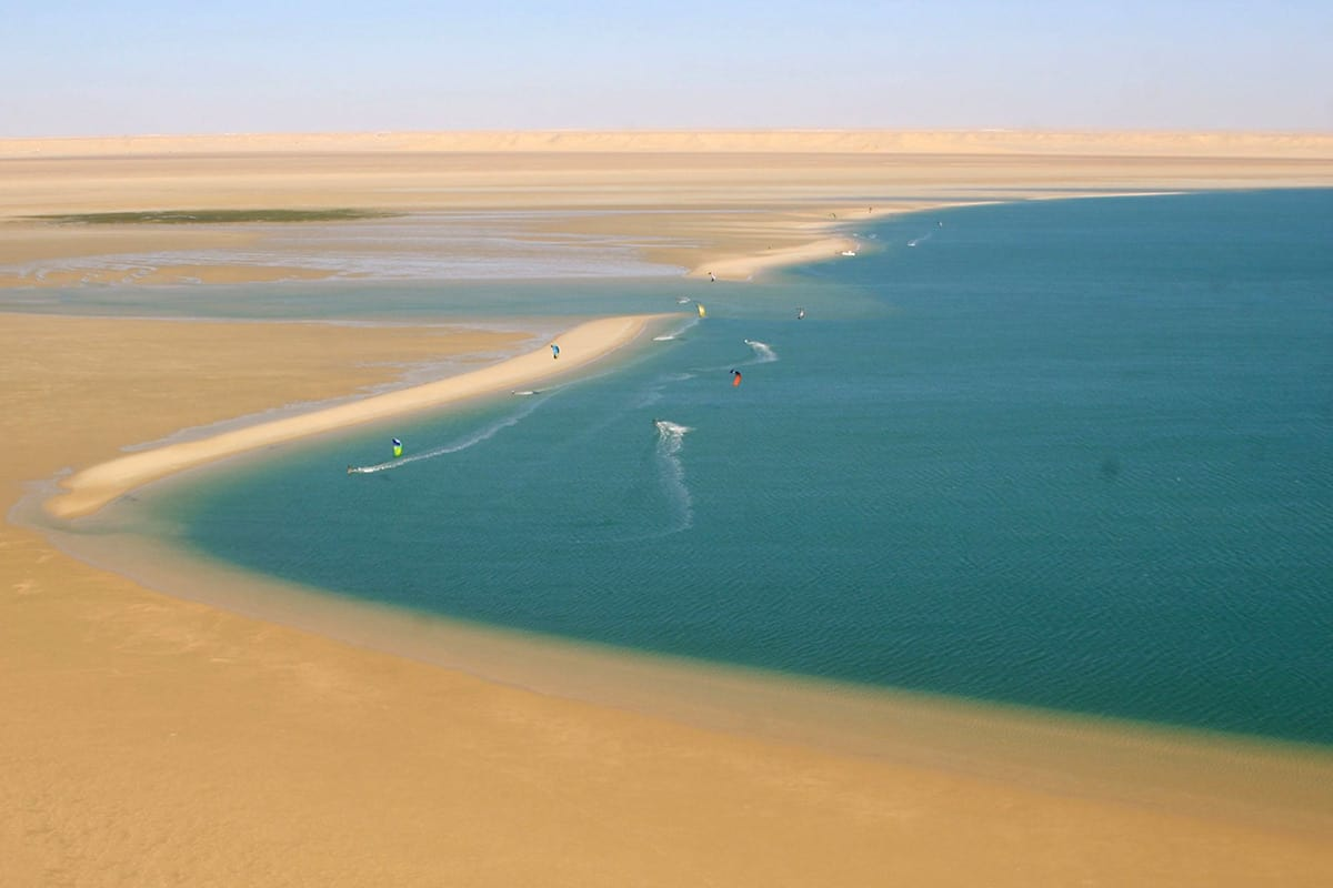 bright blue water on the right meets with golden sand of dakhla's desert on the left. we can barely see about 5 kitesurfers on the water.