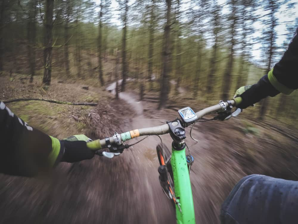 POV shot of a person downhill mountain biking through the forest on a single track. bright green bike and the rider is wearing gloves, black sleeves, and jeans