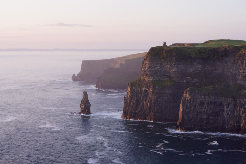 soft pink light at dusk at the cliffs of moher in ireland. The cliffs are covered with green grass and rocky faces on the right of the picture, while the swirling water of the sea covers the left.
