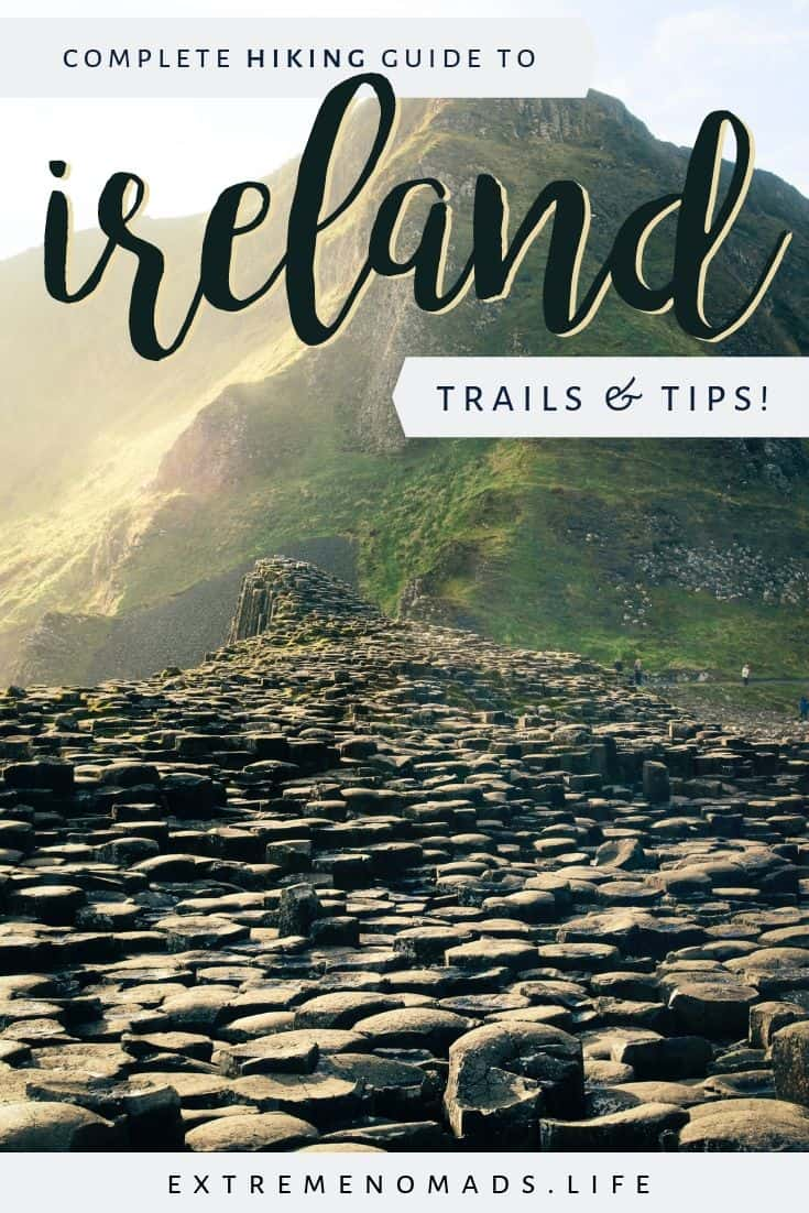 "pinterest image with picture of the giant's causeway with its hexagonal rocks and grassy mountain in the background. the image has a caption which reads ""complete hiking guide to ireland: trails and tips!"""