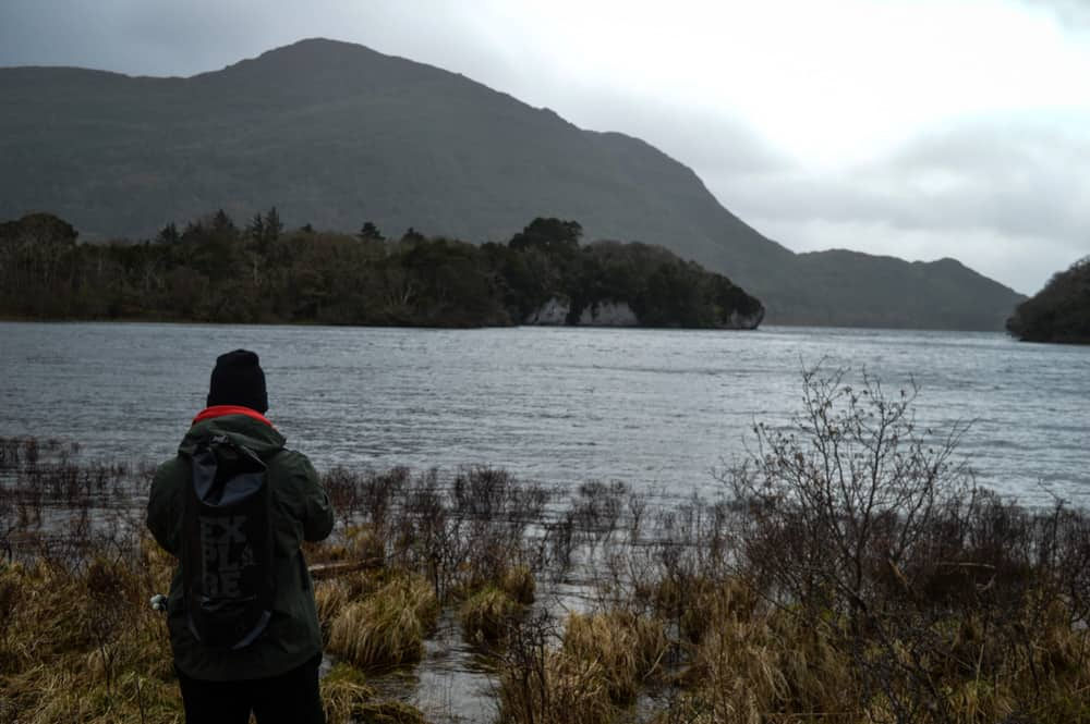 a person wearing a hat, raincoat and backpack stands with their back to the camera facing out over a lake and mountain scenery in killarney national park on a grey cloudy day