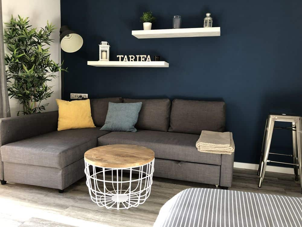 corner of a living room, featuring navy blue walls, a grey couch and coffee table, and white shelves with some candles and a small sign that reads 'tarifa'