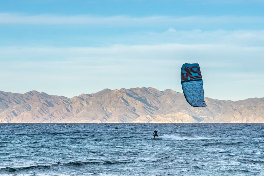 kitesurfer wearing a wetsuit riders from right to left, flying their blue kite above. in the background there are mountains standing against a pale blue sky