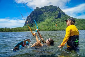 a kitesurfer and her instructor in the water in front of a jungle covered mountain. the student is laying in the water preparing to steer her kite for a water start.