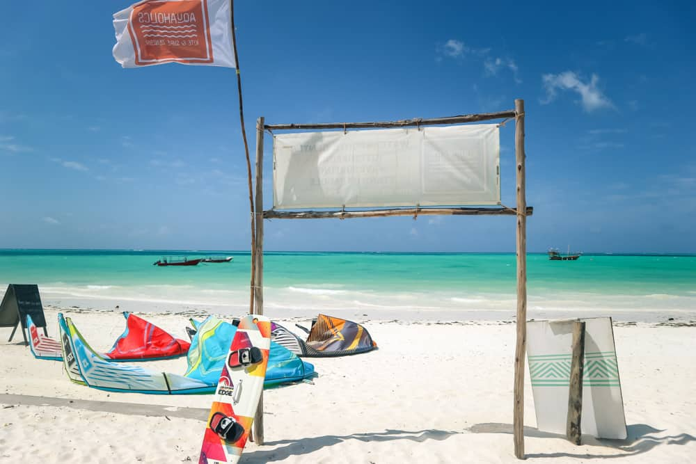 windy kitesurfing beach in zanzibar, tanzania. white sand covers the foreground where 3 colourful kites are laying. a board and flag lean against a sign that faces out over azure water.
