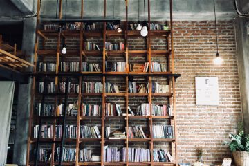 a floor to ceiling bookshelf against an exposed brik wall in a hip cafe in chiang mai, thailand