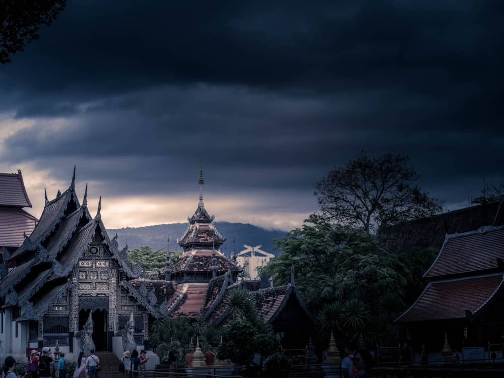 a dark moody scene of a temple in chiang mai, thailand, under a sky filled with black storm clouds