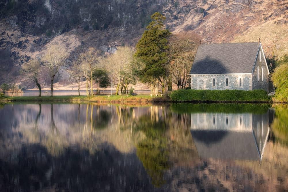Die Kirche von Gougane Barra, umgeben von einem ruhigen See. Die kleine Kirche und die dahinter liegenden schilfbewachsenen Berge spiegeln sich auf der ruhigen Wasseroberfläche