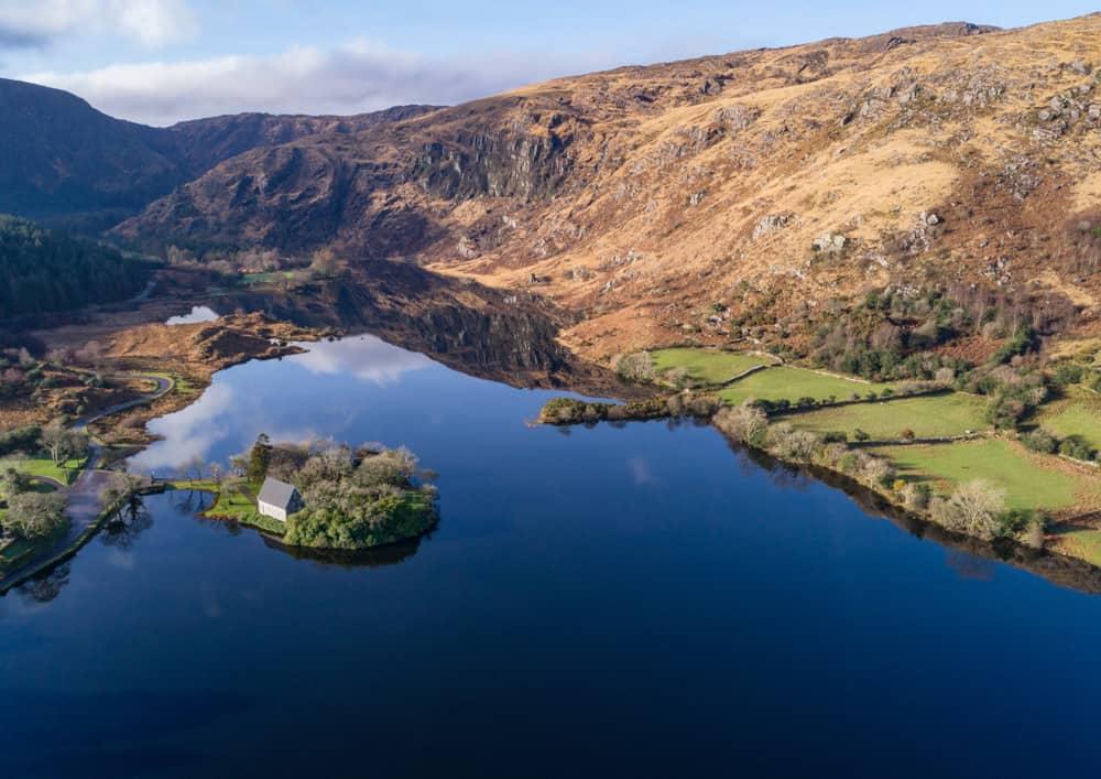 Luftaufnahme von Gougane Barra mit der Kirche auf ihrer eigenen kleinen Insel unten links im Bild und dem See und den Bergen, die sich über den Rest des Bildes ausbreiten.