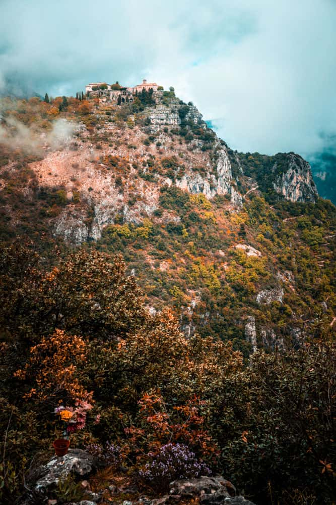 The village of Gourdon perched up on top of a misty cliff. Clouds enshroud some of the village and a portion of the mountain. The cliff face is tinged with orange and lush green foliage. Some wildflowers are growing in the foreground of the picture
