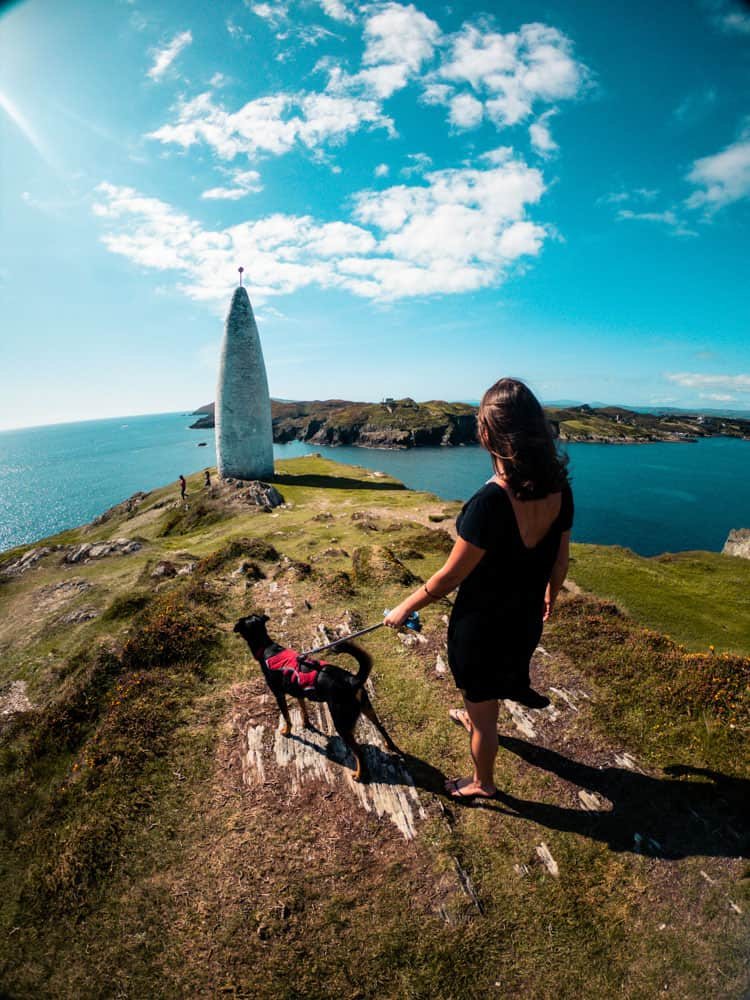 Grace and Blacky the dog standing on a cliff facing the Baltimore Beacon, County Cork. The blue sky is filled with fluffy white clouds and the scene overlooks Sherkin island.