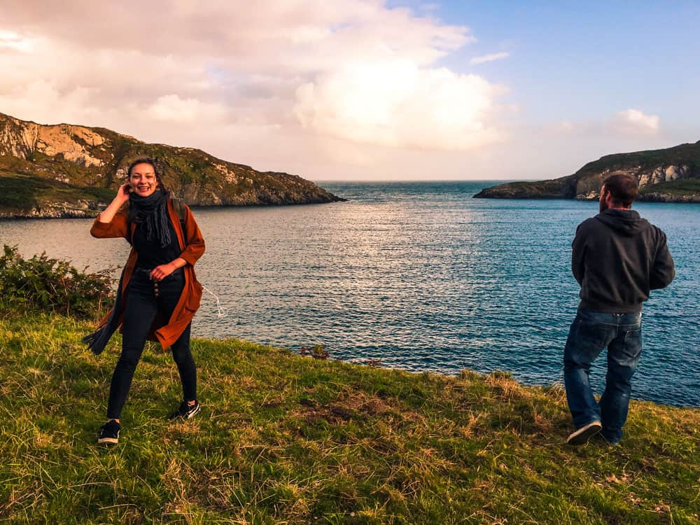 Two friends standing on the coastline overlooking Horseshoe Bay, Sherkin Island, County Cork at sunset.