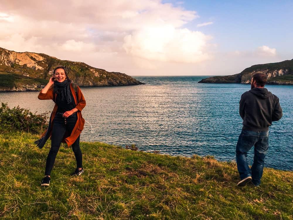 Dois amigos em pé na costa com vista para Horseshoe Bay, Ilha Sherkin, Condado de Cork ao pôr-do-sol.