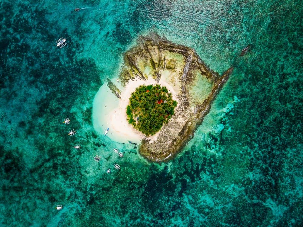 aerial view of guyam island off the coast of siargao island, philippines. the tiny island is a diving location, surrounded by turquoise water and coral reef.