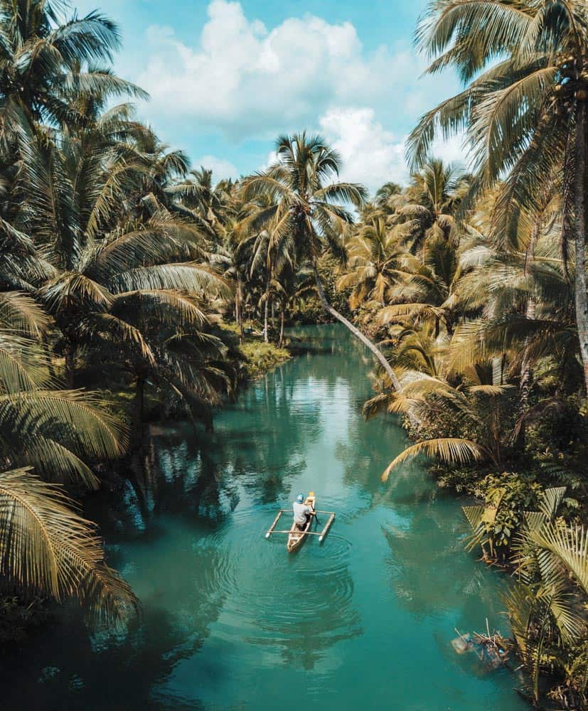 A fishing raft floating on a turquoise river surrounded by palms on Siargao island, philippines
