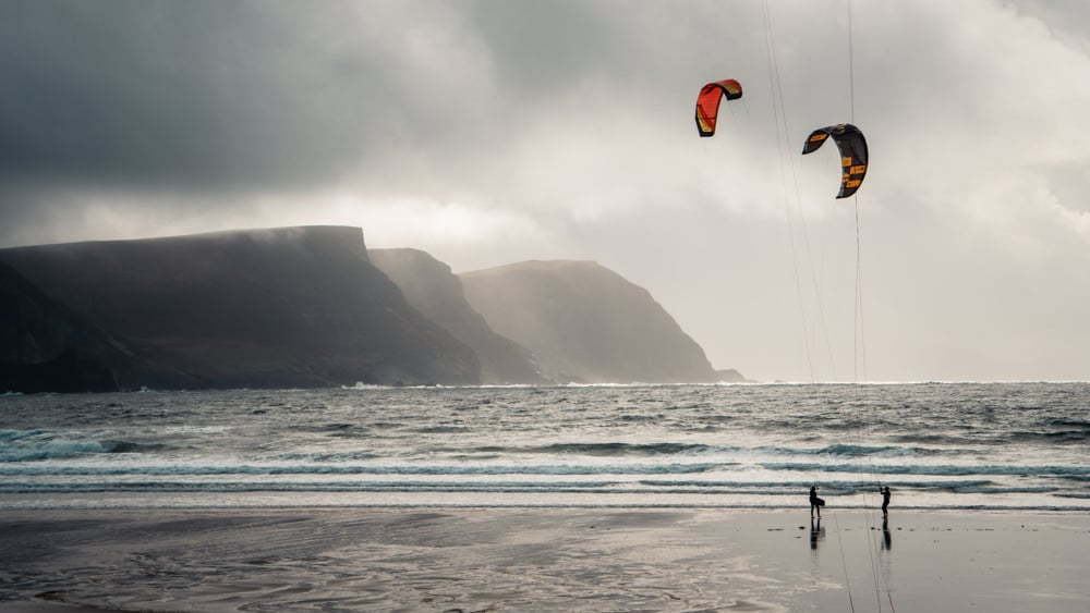Two kitesurfers standing with their kites in the air on Keel Beach, Achill Island, County Mayo, Ireland. The misty mountains in the back left of the photo are almost totally enshrouded in cloud. It's a grey, wet day.