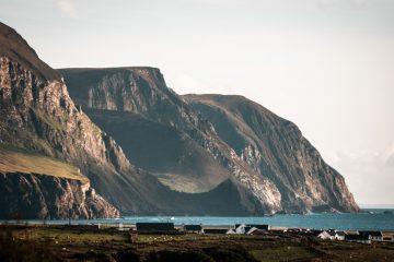 Dramatische Meeresklippen am Kieler Strand, Achill Island, Grafschaft Mayo, Irland. Das Wasser in der Bucht ist leuchtend blau und die Klippen werden von der Sonne zur goldenen Stunde beleuchtet. Ein paar Häuser liegen am Fuß der Klippen.