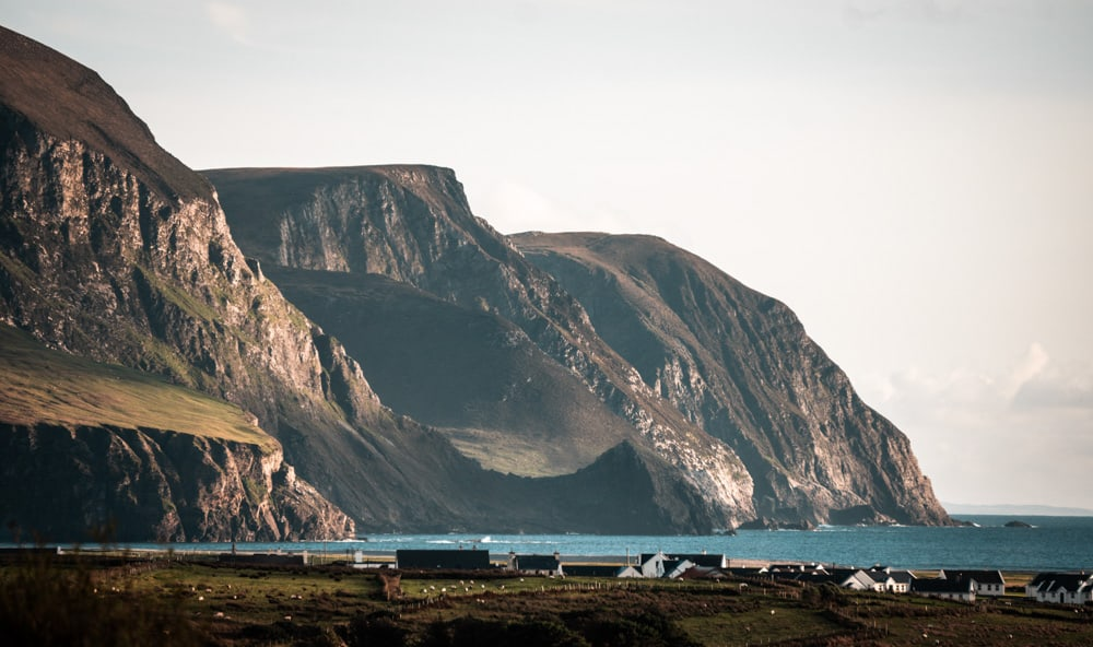 dramatic sea cliffs at keel beach, achill island, county mayo, ireland. The water in the bay is bright blue and the cliffs are lit up by the sun at golden hour. A few houses lie at the foot of the cliffs.