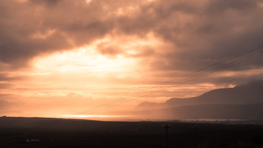 tangerine sunset on achill island, county mayo. the sky is filled wihtmist and clouds, the sun is barely shining through. sea cliffs can just be seen in silhouette.