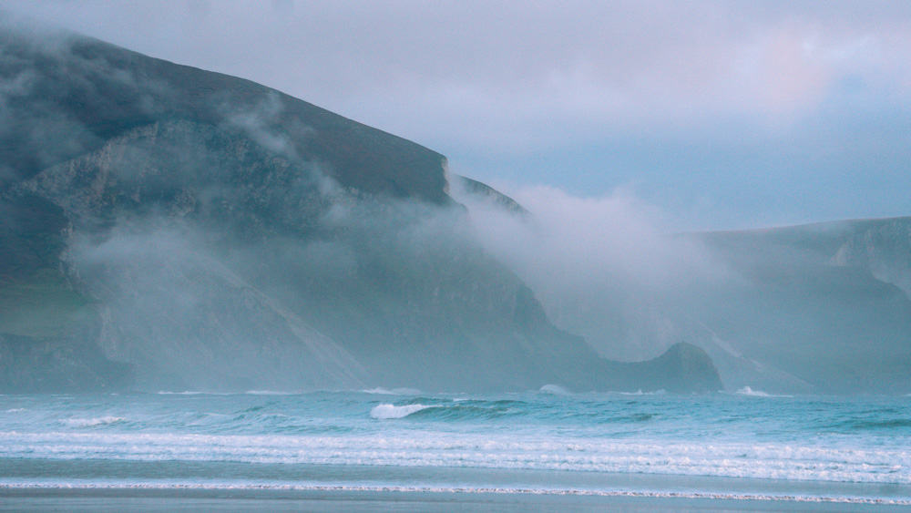 the misty sea cliffs at keel beach, achill island, county mayo (ireland). waves are rolling in at the foot of the cliffs