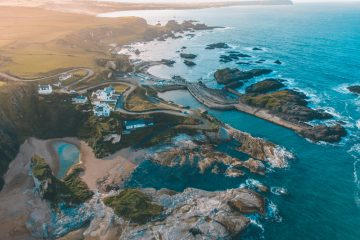Aerial shot of Ballintoy Harbour in the north of Ireland. The water is a beautiful blue and a flare of light is creeping over the coastal landscape from the top left. There is a snaking road winding through a handful of houses near the craggy coastline.