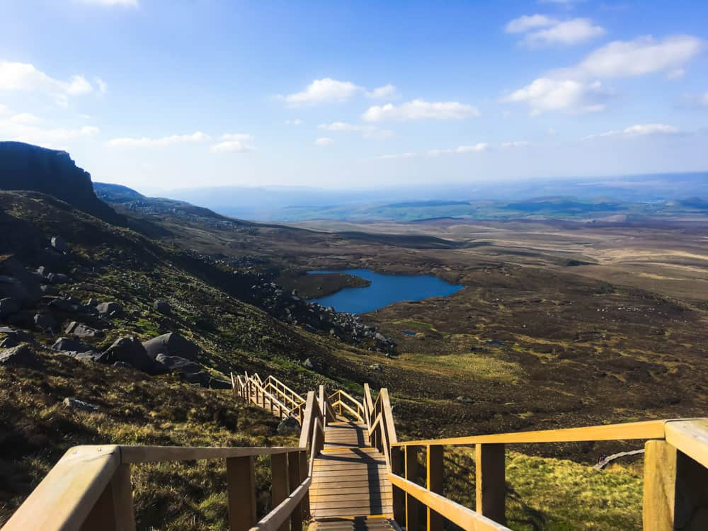 Ireland's Stairway to Heaven, shot from above. The wooden staircase creeps up the side of a craggy mountain overlooking a lake and vast landscape.