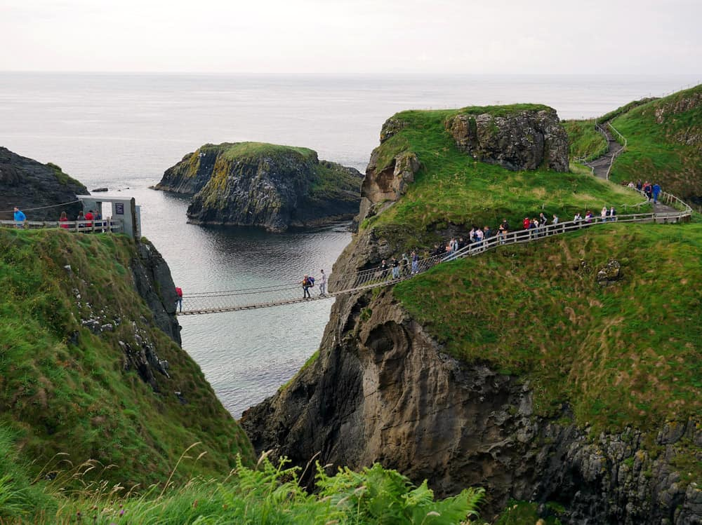 Carrick-a-rede rope bridge from a lookout point. Many people are crossing the spindly bridge which connects two green grassy hills, separated by a cavern.