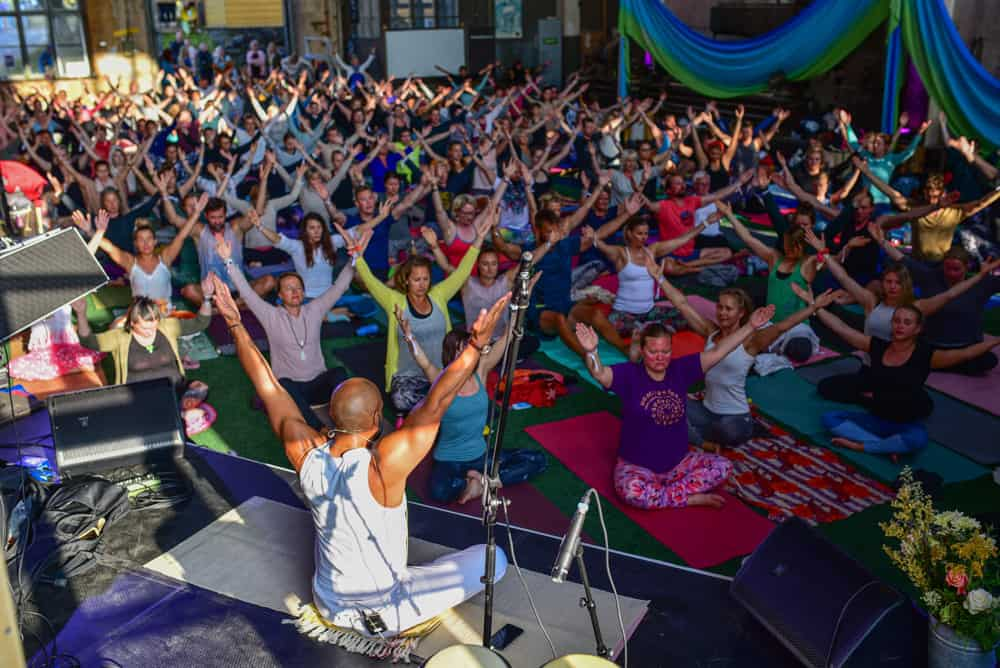 a crowd of people seated on yoga mats doing asanas while led by a teacher on a stage