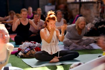 A woman dressed in black and white in a pool of light, in a seated yoga position with her palms raised upwards in front of her face. She's in a crowd of people doing yoga.