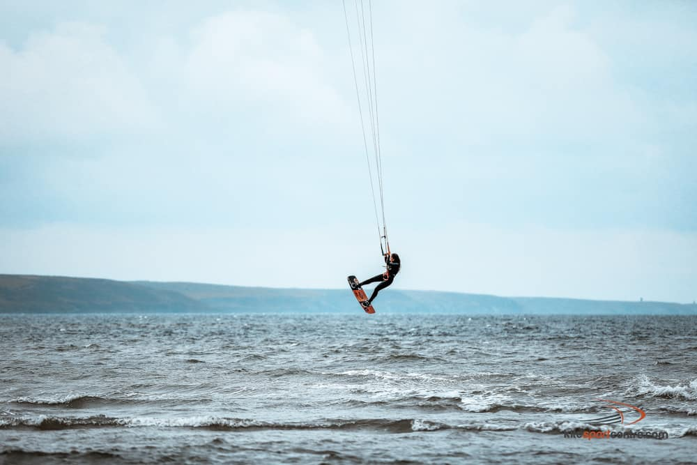 a kitesurfer wearing a black wetsuit jumping above the flat-ish water somewhere in ireland.