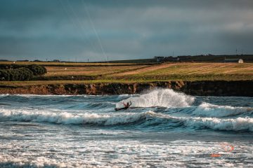 a kitesurfer wearing a blue and orange wetsuit rides in the choppy shore break in front of some farmland in ireland.