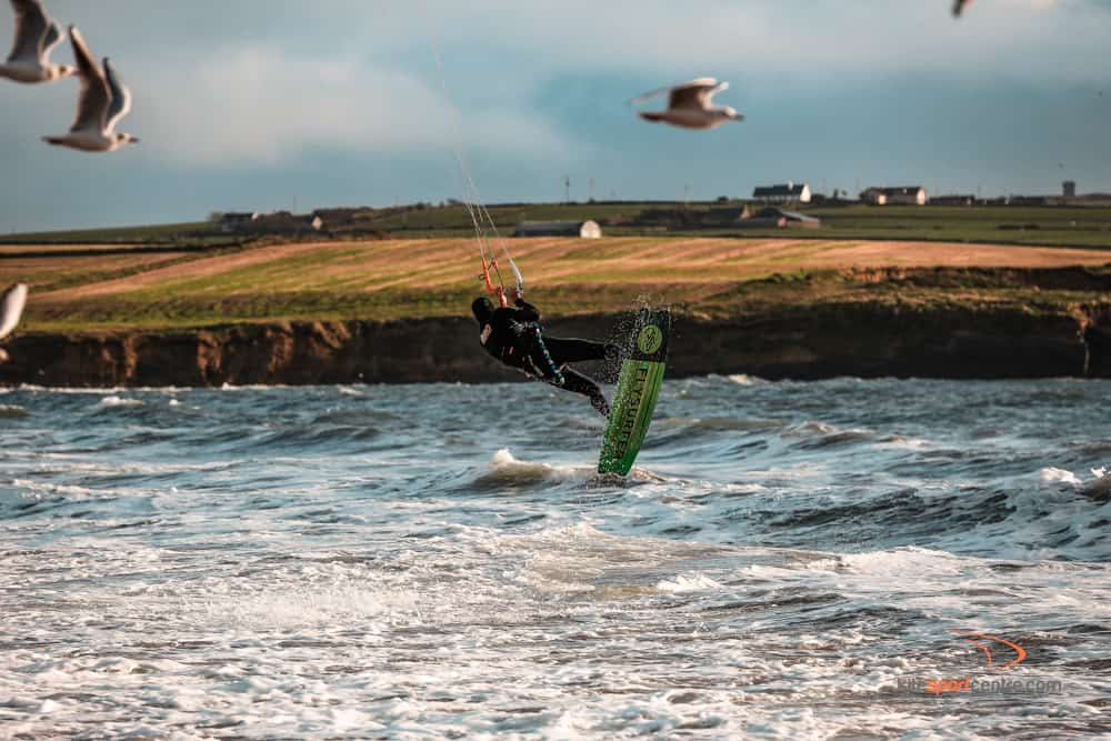 a kitesurfer wearing a black wetsuit jumps over the water. seagulls are flying around him and we can see farmland in the background.