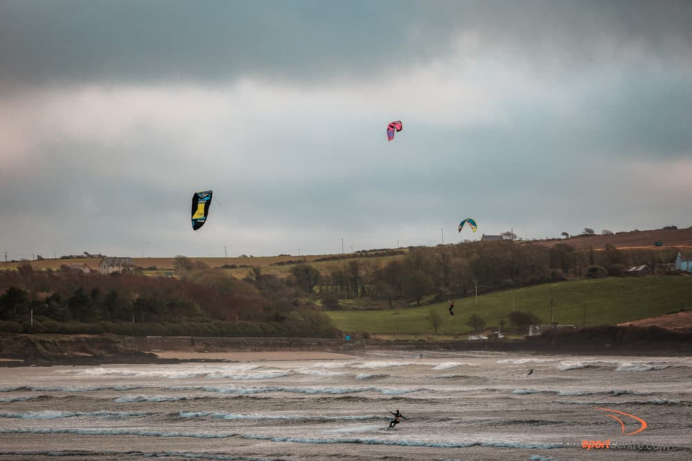 a moody cloudy day at the kitesurfing beach in ireland. three kites fly in the air.