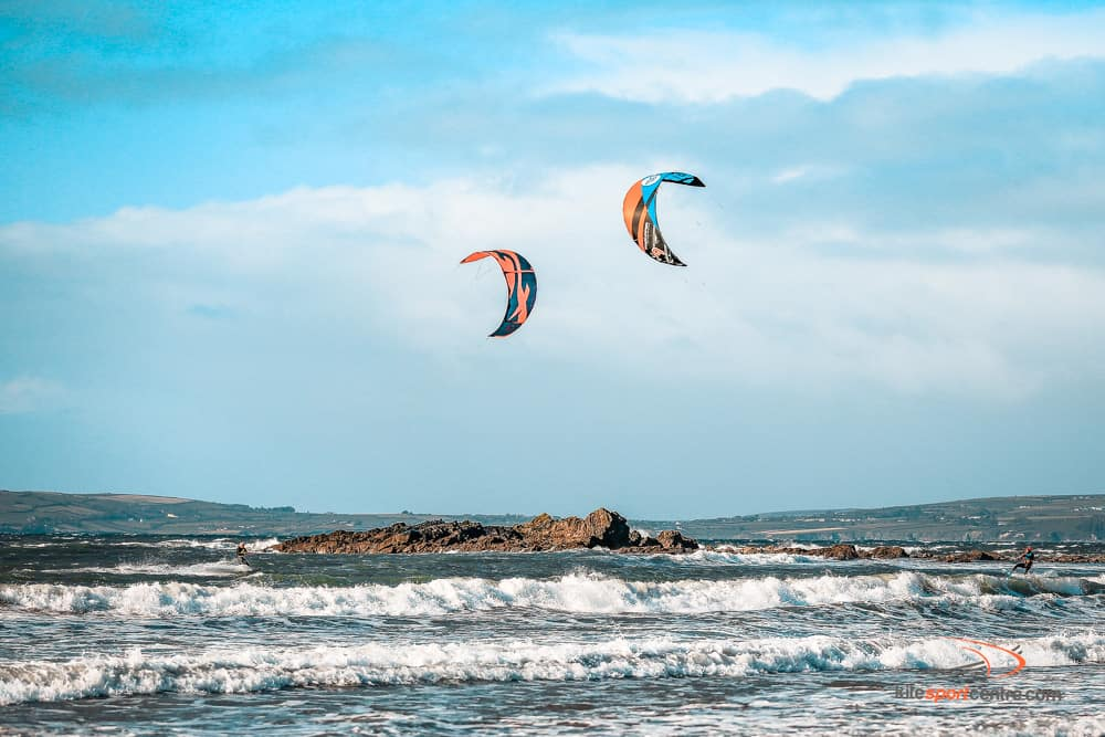 two kitesurfers riding towards each other in the choppy irish waters. there are craggy rocks sticking out of the water and the coastline is just visible behind.
