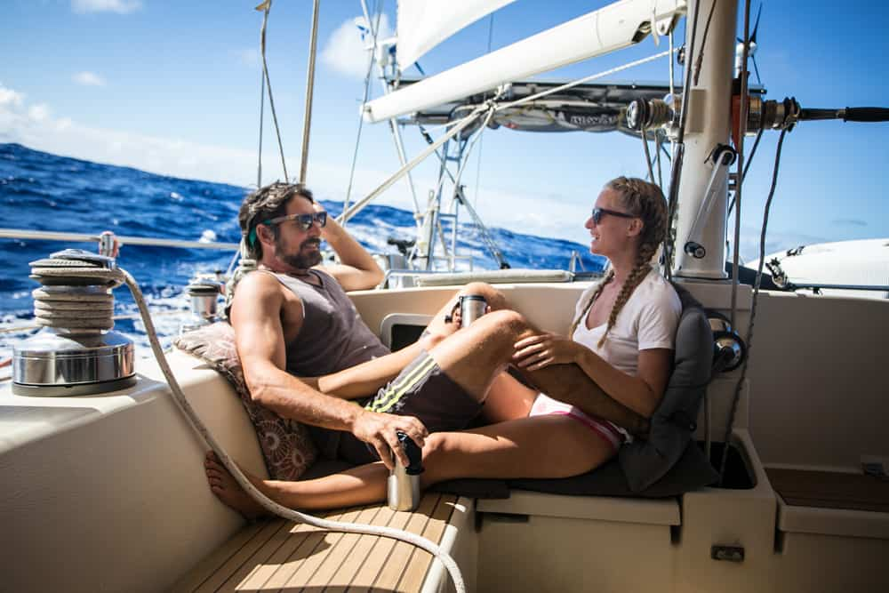 Brian and Karin sitting onboard SV Delos, cruising through the ocean on a sunny day