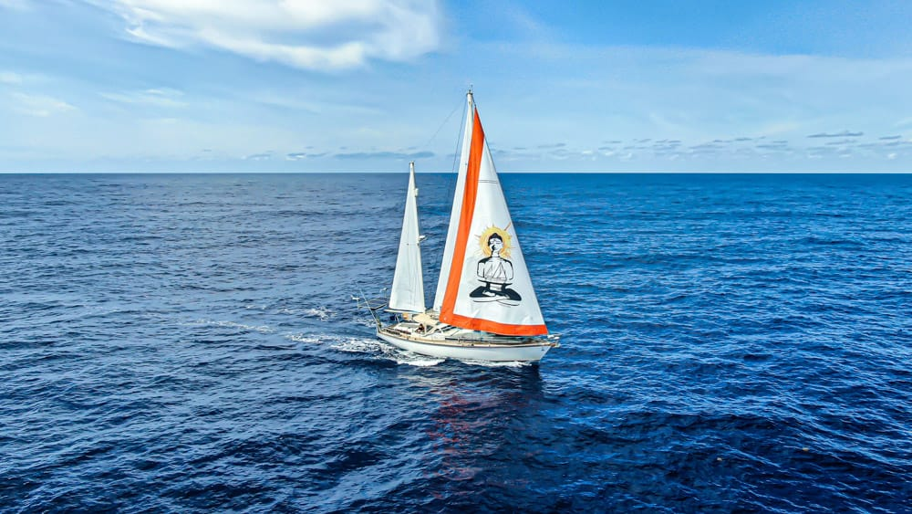 SV Delos sailing through the open sea. The sails are up, the water is calm, and the sky is blue