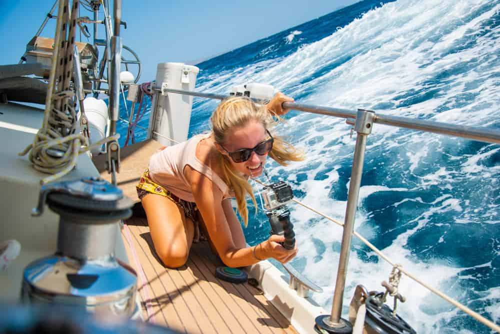 Karin from SV Delos kneeling down on the deck of the sailboat shooting the action on a GoPro.