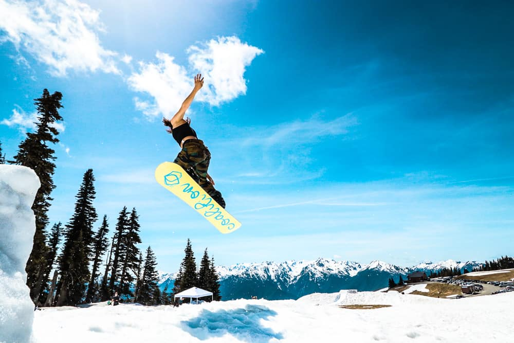 woman snowboarding on a coalition snow snowboard for women. the sky is bright blue over the snowy mountains, with some evergreen trees on the lefthand side of the frame.