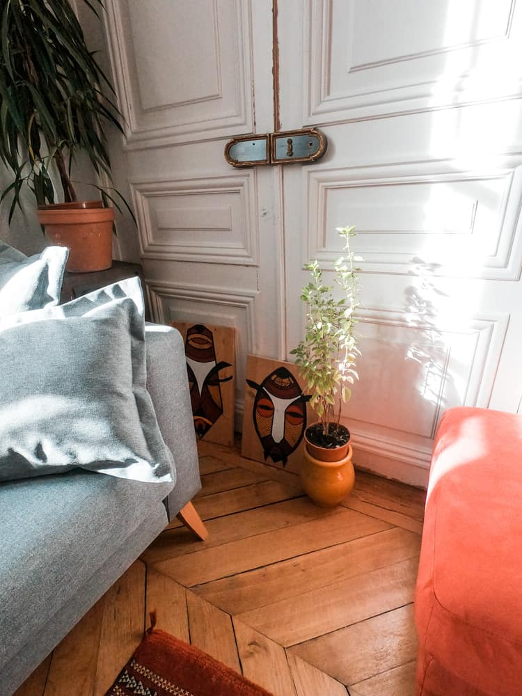 nicely decorated corner of the cloud citadel coliving space. the edge of the couch meets with a potted plant, two pieces of tribal artwork, and the old parquet flooring