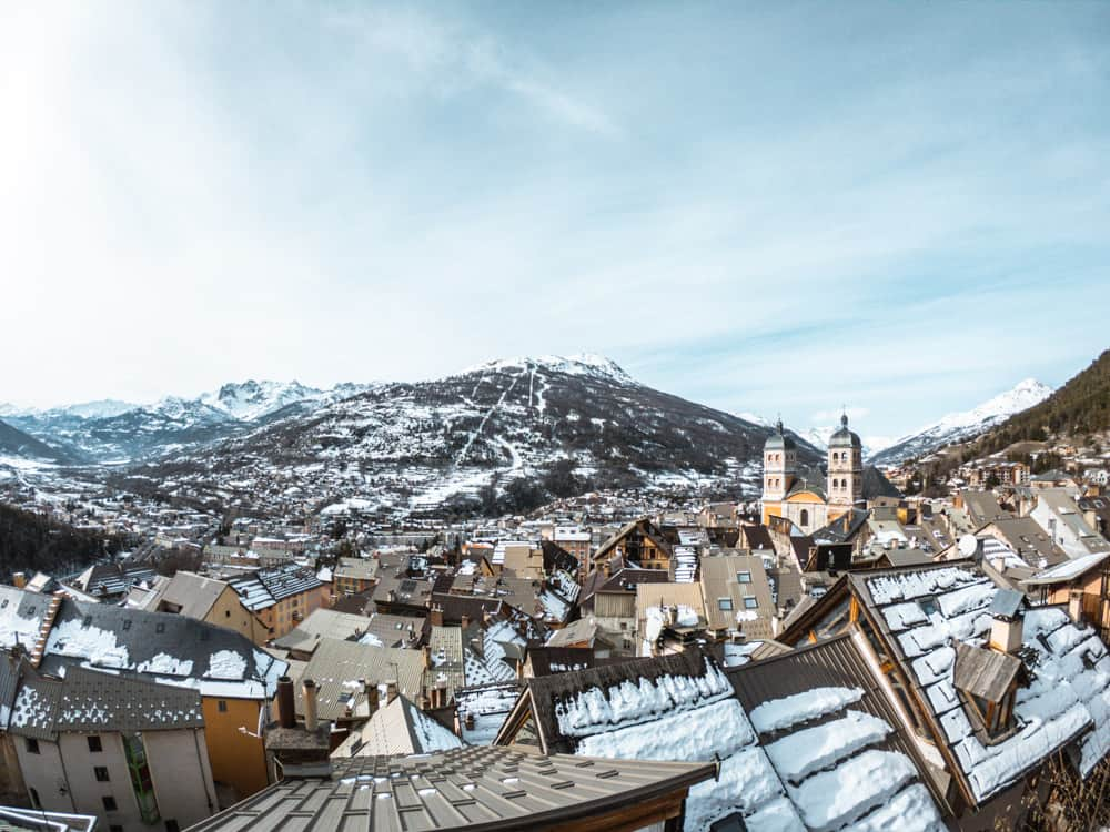 View of Briançon old town from on top of the old barracks. snow capped mountains sit in the background. the sky is blue. the roofs of the town are covered in snow.