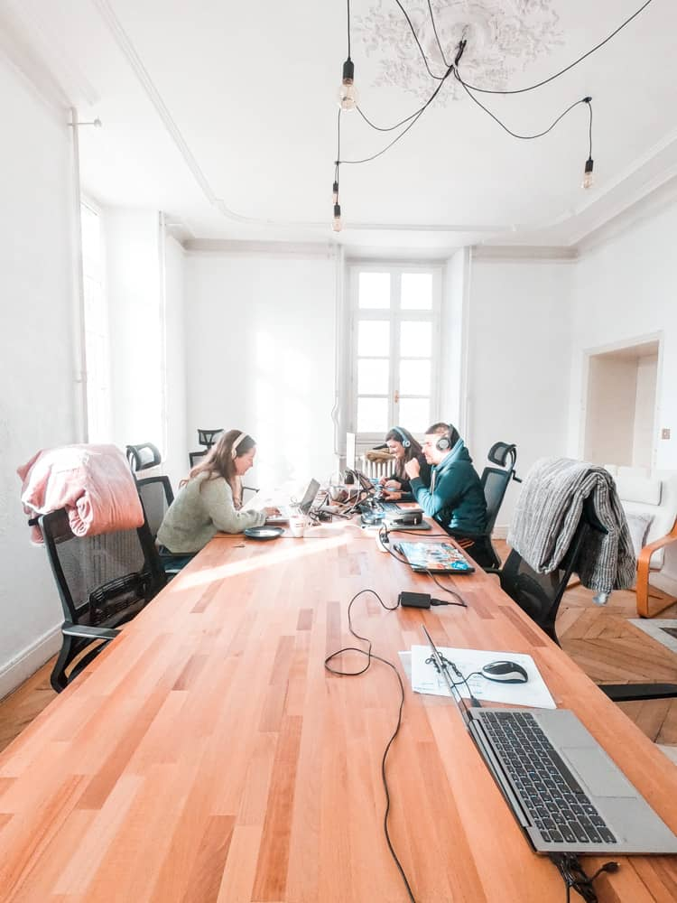the coworking room in cloud citadel. there are three people working on their laptops wearing headphones.