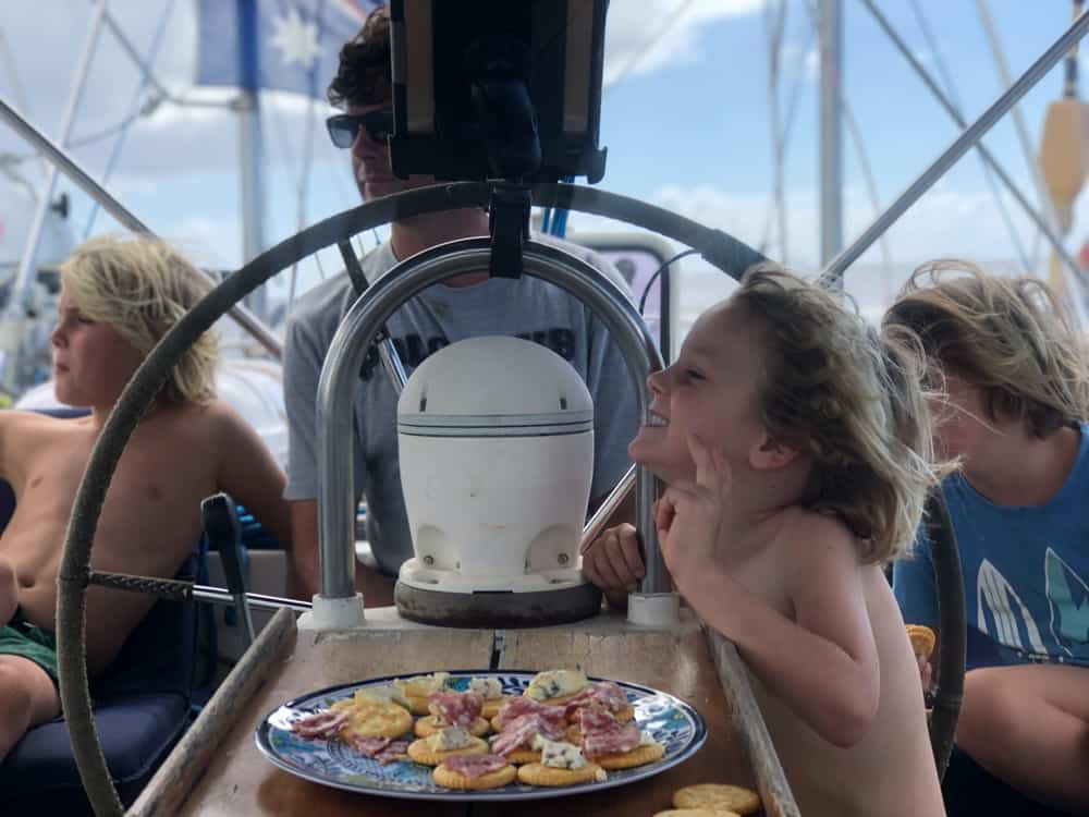 three blond kids relaxing on a sail boat with dad at the wheel
