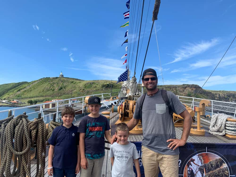 three kids and dad standing on deck of a sailing boat moored near the shore. The sky is bright blue and the weather is fabulous. They're all smiling and have their arms around each other.