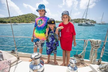 three kids decked out in colourful shirts, standing on the deck of their sail boat. The boat is floating on incredible turquoise water. There are a few other sailing vessels floating i the background.